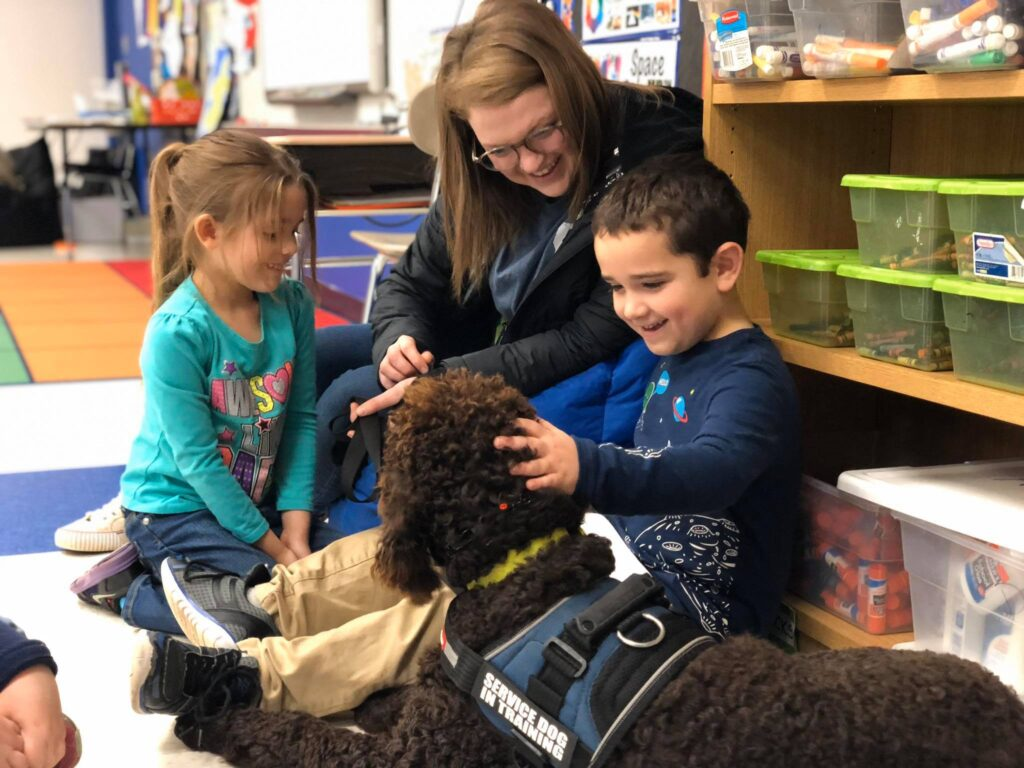 service dog trainer with dog and child at reading program
